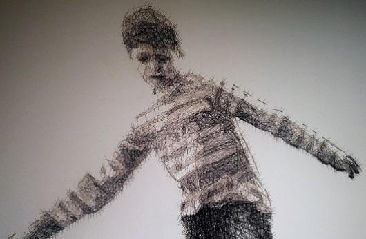 פרט מתוך 'הולך על חבל מתוח', דבי סמית, 2016. לא כל כך רואים בצילום, אבל הילד עשוי כולו מחוטים דקים שמתוחים בין סיכות תפירה