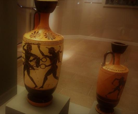 לקיתוס (כד לשמן) ועליו תיאור של הרקולס נאבק באפולו, יוצר בין השנים 500-510 לפני הספירה. המאבק בין השניים הוא על חצובת הברונזה המקודשת של דלפי, מקום מושבה של הפיתיה בזמן שהיא מוסרת נבואות מטעם האל. הרקולס מחזיק את החצובה ורץ, תוך שהוא מביט לאחור ומאיים על אפולו שמאחוריו. בעקבות אפולו מגיעים שני אלים: אחותו ארטמיס, והרמס / צילום: גלית חתן